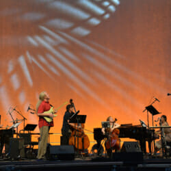Bang on a Can All-Stars playing onstage against an orange background